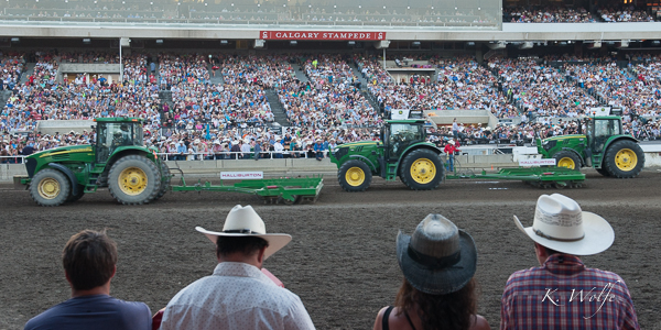 Getting the track ready. I see rhythm in the tractors, the crowd in the background and the cowboy hats in the foreground.