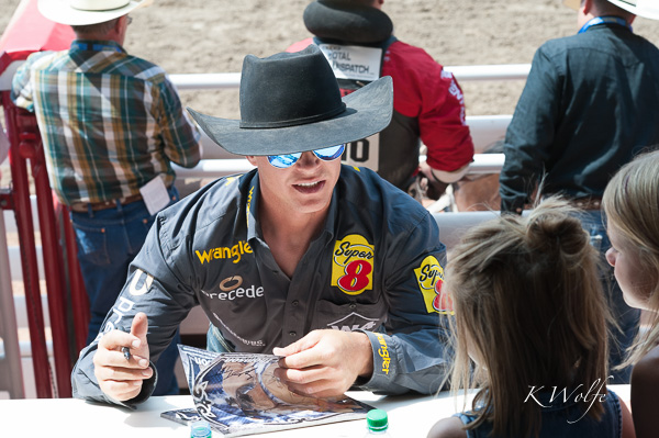 Close enough for one of the saddle bronc riders to sign autographs for the big kids.
